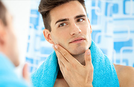 man with towel looking in mirror